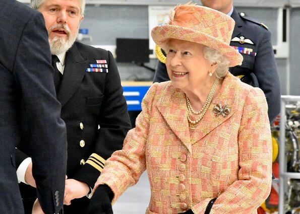 As Honorary Air Commodore, Queen Elizabeth. She wearing a peaches and cream outfit with matching hat by Angela Kelly. diamond bow brooch