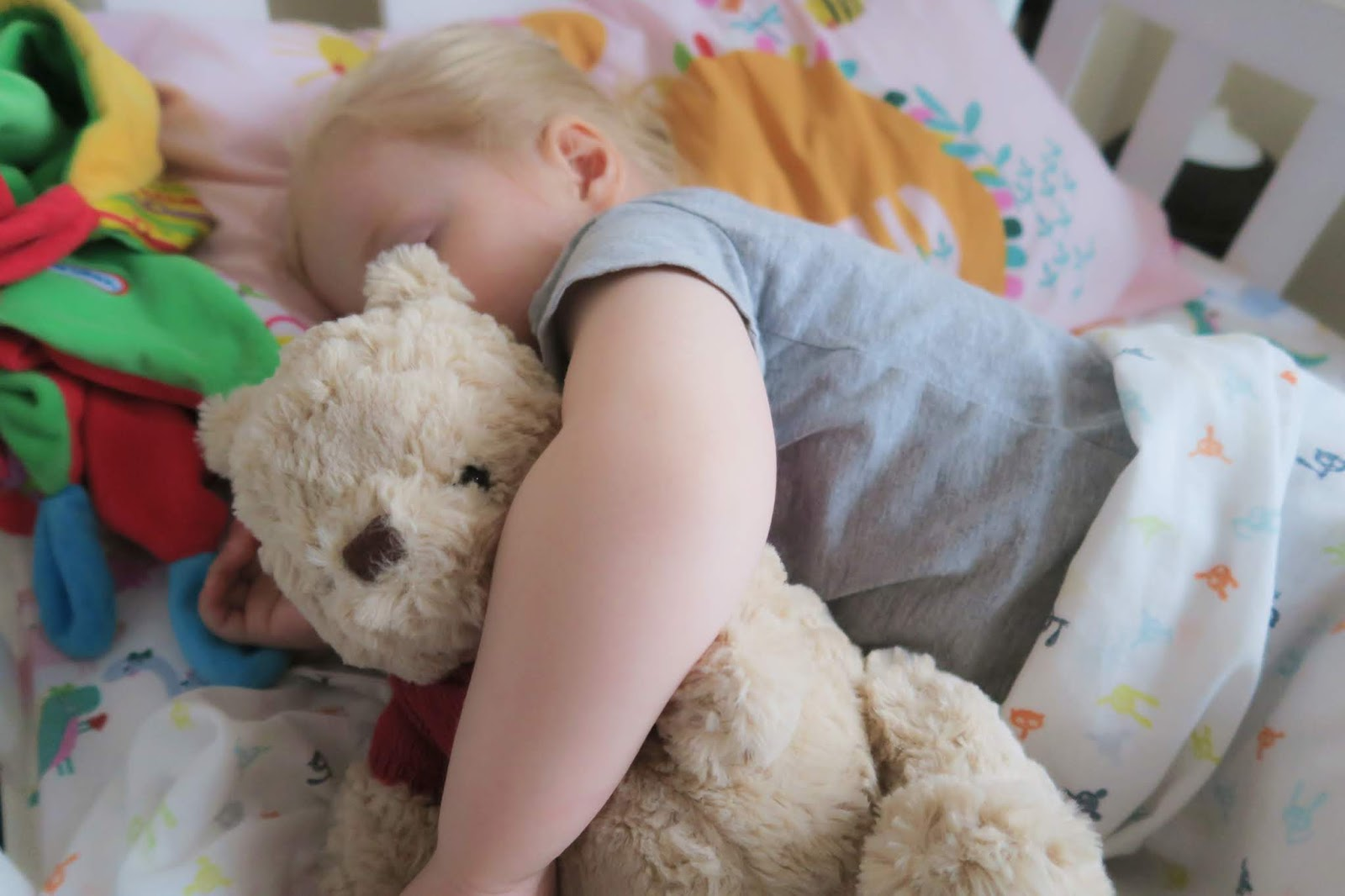 Elise asleep in bed and cuddling the winnie the pooh plush