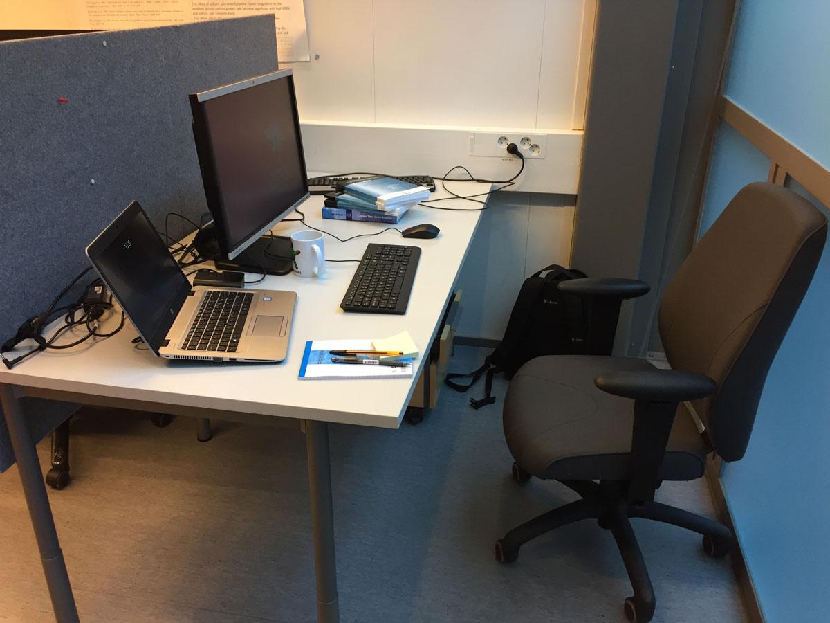 Työpöytä toimistossa, pöydällä läppäri, näyttö ja kirjoja.