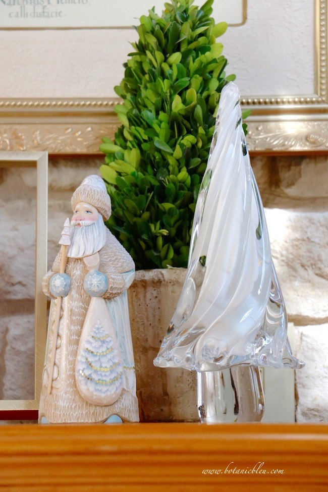 Create a neutral Christmas color scheme with a hand carved wood Santa and white glass tree