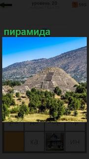 среди зеленых насаждений стоит высокая пирамида