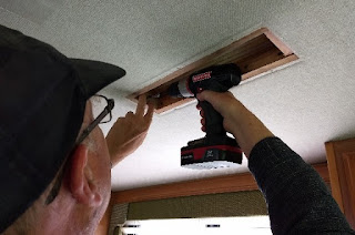man drilling a piece of wood re-framing a section of motorhome ceiling