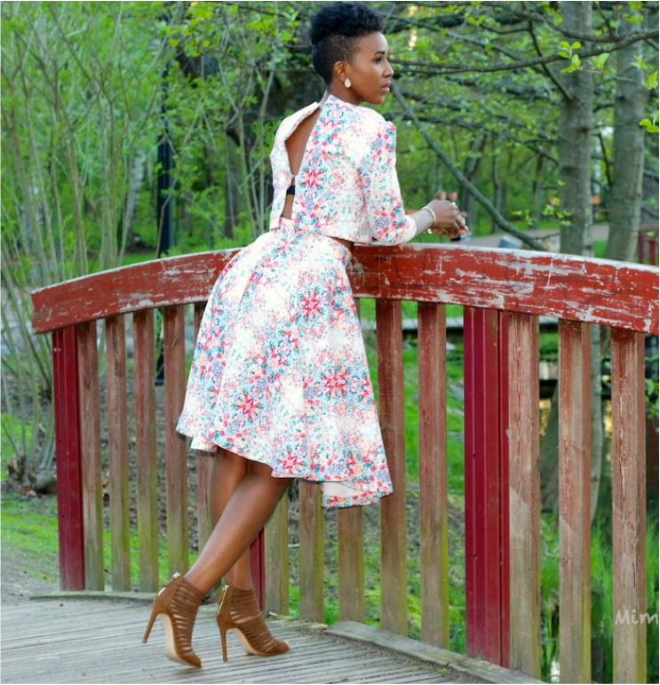 woman in flowerly outift and a pair of dark brown heels Zara heels leaning on a red bridge
