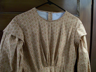 Smooth gathered bodice, bishop sleeves, and sleeve caps on girl's 1850s dress.