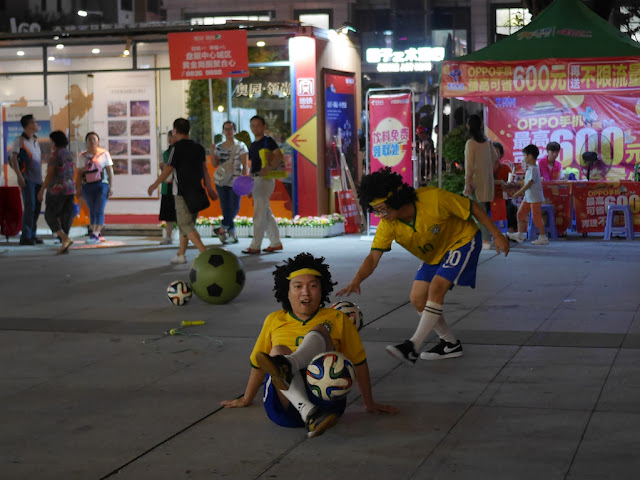 two young men wearing wigs doing a soccer show in Zhongshan