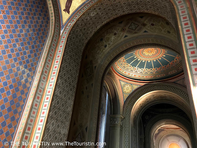 Blue, red, gold, green coulred vaulted ceiling in a church.