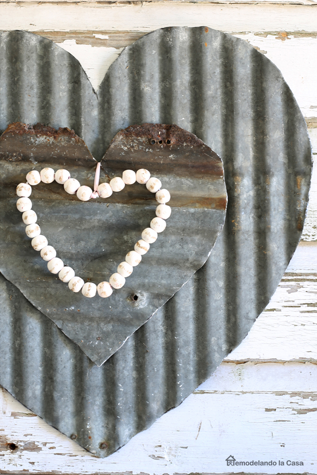 two corrugated metal hearts a top chippy planks wall art.