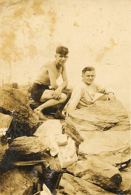 Two young men sitting on large rocks at a beach. They are unidentified, but appear in other photos from an album belonging to Estelle Karvoius. Privately held by E. Ackermann, 2016.