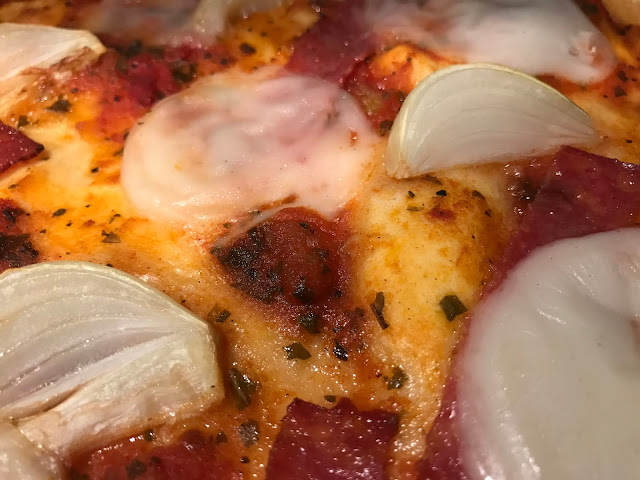 A close up photograph of homemade pizza with a tomato sauce, onions and circles of dairy free Mozzarisella pizza