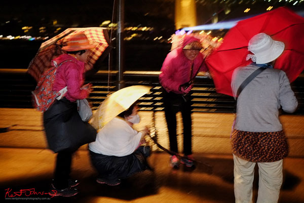 Ladies with umbrellas laughing in the rain, Vivid Sydney 2013