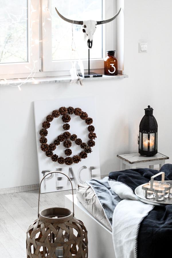Schlafzimmerdeko im New Boho Look mit schwarz-weißen Ethnoelementen und Holz Accessoires, Bohoschädel, afrikanische Maske und Bambus-Laterne; DIY Bild mit Peacezeichen aus Tannenzapfen