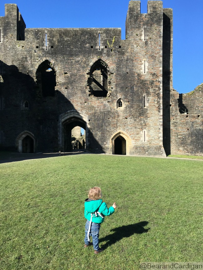toddler on grass in front of ruins