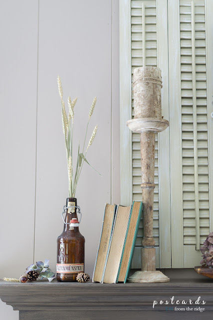 old books and vintage beer bottle with tall wood candlestick on mantel