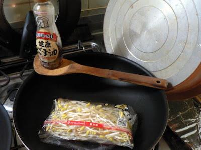 豆もやしをごま油で炒める