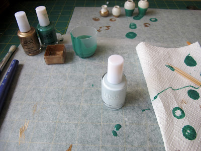 Workbench with baking paper and a paper towel dotted with bits of nail varnish, with nail varnish bottles and dipped dolls' house vases in the background.