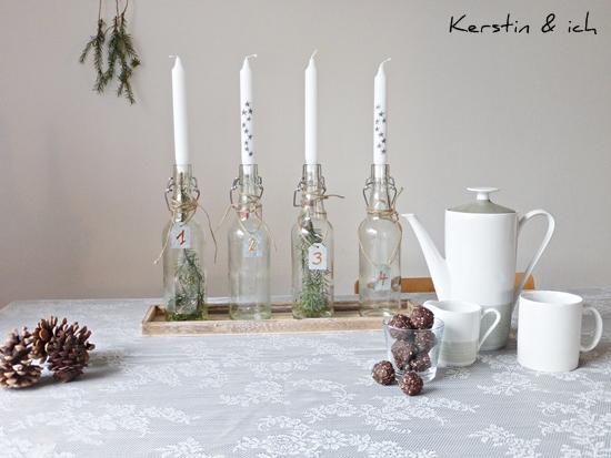 DIY-Adventskranz mit bemalten Kerzen und Tannenzweig in der Glasflasche