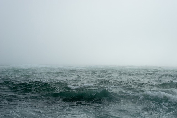image of a turbulent sea beneath a misty sky