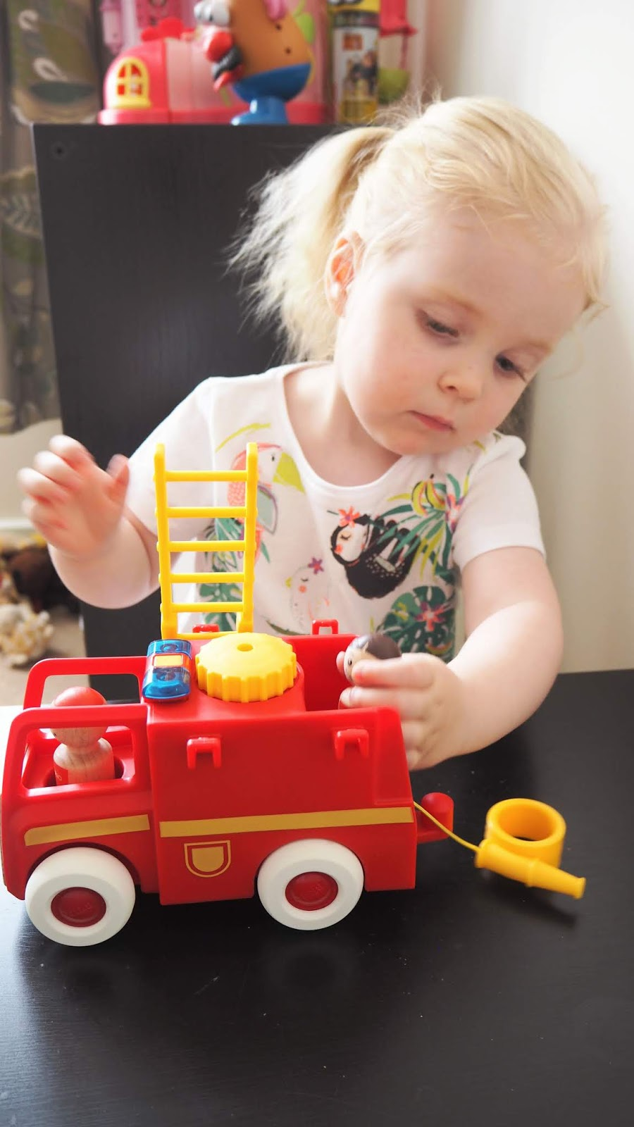 The fire truck is in the foreground with Elise in the background. She is lifting a little wooden person onto the back of the fire truck toy.