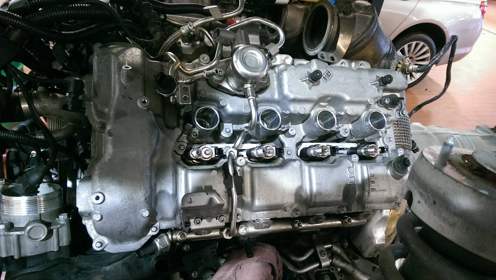 That round thing with the metal lines going into it is one of the high  pressure pumps. They are located on the top section of the valve cover, ...