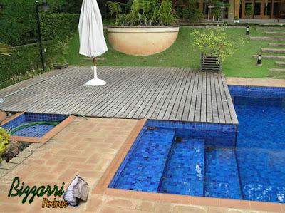 Construção da piscina de alvenaria com revestimento de pastilhas com o passeio da piscina com tijolos e a execução do deck de madeira com a escada de pedra.