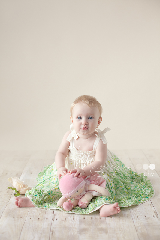 Pretty baby girl with doll wearing a cream and green dress