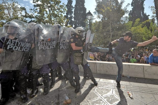 A Greek protestor kicks riot police right in the shield