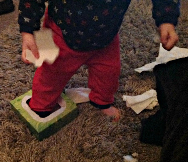 picture of a toddler with his foot in a tissue box