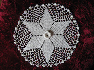 Top view of Irish Rose jug cover worked in white size 20 cotton thread. It is edged with glass beads to weigh it down and prevent it from slipping off the top of a jug or cup.  The star shape is made of Australian/UK treble stitches and the centre motif is an Irish rose.