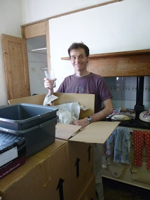 Picture of my husband unpacking boxes in the kitchen and holding a glass, after moving day when we moved to the country