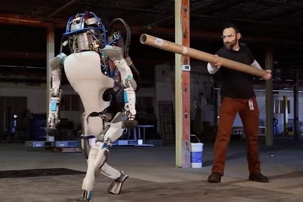человек толкает робота палкой инженер бьет робота атлас издевательство над роботом