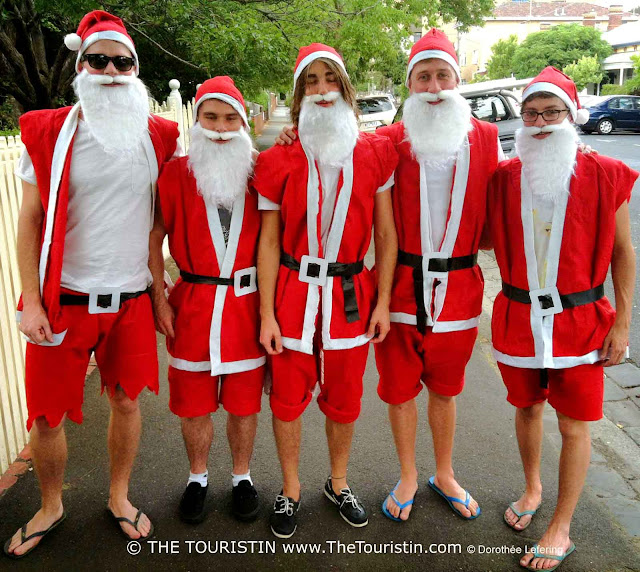 Five young men dressed up as Santa Claus with short red bermudas and flip flops.