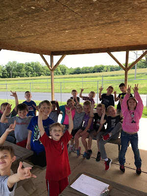 First grade students sitting on a bench with their hands in the air smiling for a picture