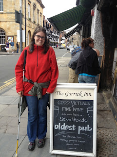 Me with my cane next to a pub sign in Stratford, England