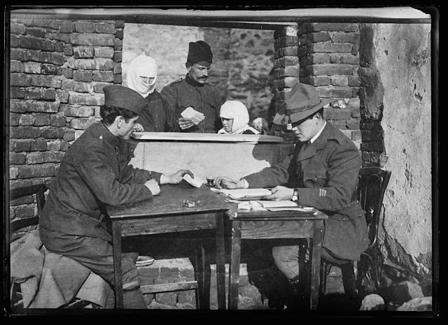 From this little desk was done the paper work that distributed relief to many thousand Serbian refugees in the Monastir district. Captain Lanning Mc Farland, a Harvard student, was in charge of the American Red Cross work in this town. He operated a bakery, hospital, bathing establishment, warehouse and feeding station. He is shown at his desk examining the application of a Turkish woman for relief