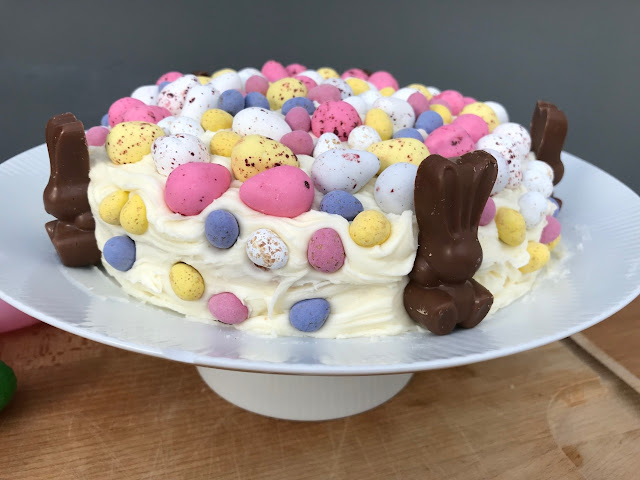 A cake covered in frosting, mini chocolate eggs and chocolate bunnies