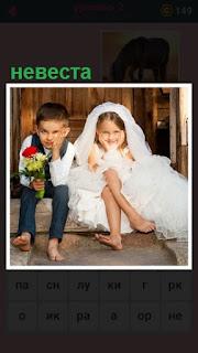 на крыльце дома сидят дети, имитируют жениха и невесту в белом платье