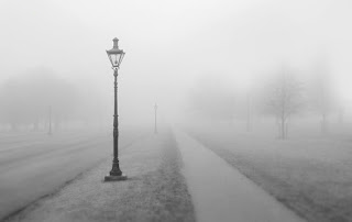 A grey photographic image of a lamp-post at the side of a path between areas of grass leading away from the frame. There are some faint outlines of trees in the foggy middle-distance.
