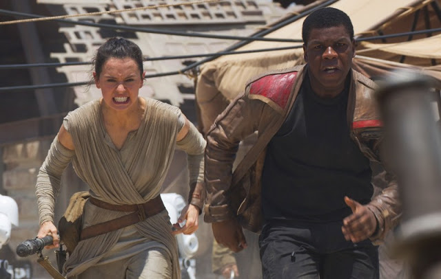 John Boyega (right) as Finn and Daisy Ridley as Rey in Star Wars: The Force Awakens, Directed by J.J. Abrams