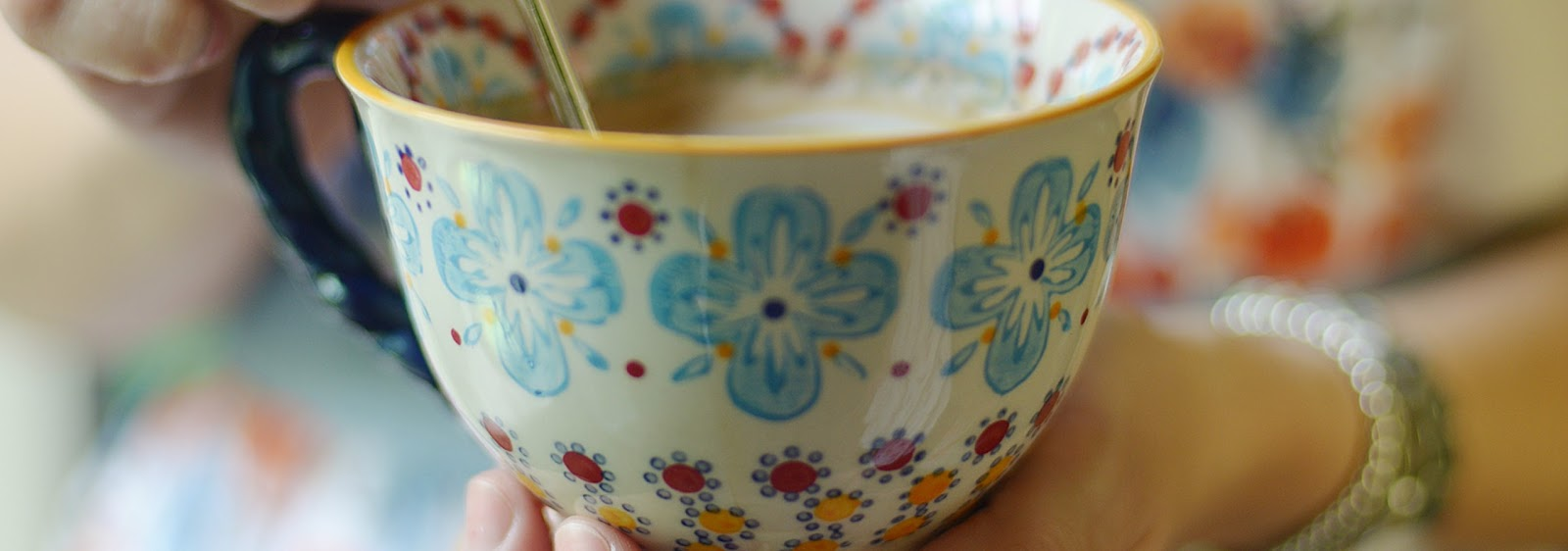 tea in a flowery mug, cupped in a pair of hands. A flowery dress in the background.