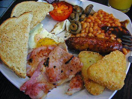 Stevig Engels ontbijt met toast, ei, spek, worst, champignons, tomaat, bonen in tomatensaus en aardappelpuree