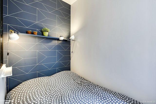 dormitorio pequeño con papel pintado como cabecero