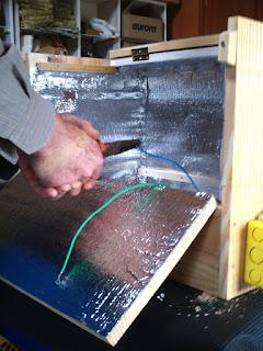 homem instalando a resistência na estufa de madeira forrada