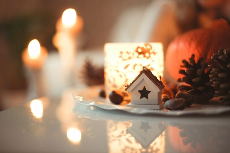 Candles, pine cones, chestnuts and a tiny wooden house as a wintery scene