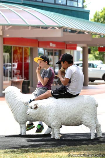 L-R: Brock Wellings, Wellington, Ray Moo, Wellington, in Hawke's Bay to watch their mother run in the Iron Maori half IronMan, eating lunch sitting on the sheep in the Hastings CBD, Hastings, in pleasantly hot sunny weather. photograph