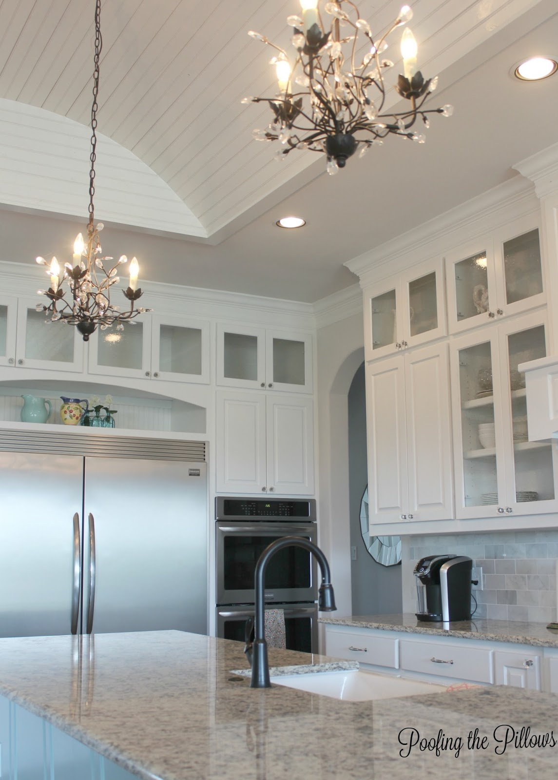 Light and and bright is the name of the game in this Texas kitchen with white cabinets, glass inserts, granite counter tops, stainless appliances and a few farmhouse touches. Sherwin Williams Water on the island and the perfect chandeliers add favorite touches.