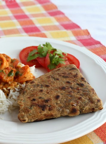 Food Lust People Love: A spicy twist on traditional plain paratha made with wholemeal wheat flour and seasoned with onion, garlic, chili peppers and cilantro as well as ground coriander and garam masala and cooked on a hot griddle.