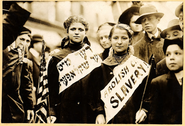 "Two young women in a May Day parade in New York City, carrying American flags and wearing ""Abolish Child Slavery"" banners in Yiddish and English (May 1, 1909)"