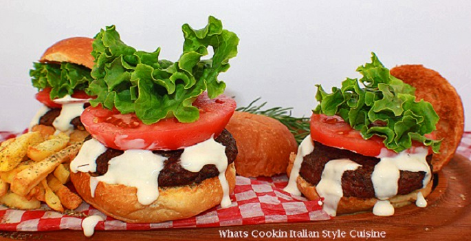 this is how to make a burger topped with Alfredo sauce. This burger also has tomatoes on it and fancy green lettuce on top with french fries on the side