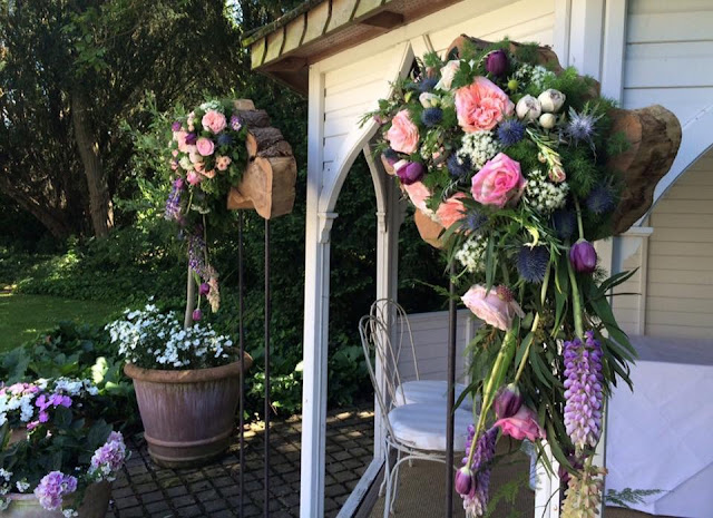 Wedding flower displays of pink and peach roses, purple tulips and blue thistles at British outdoor wedding gazebo