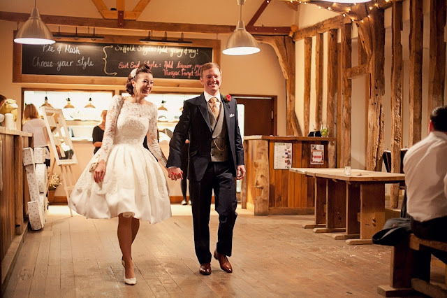 A bride in a knee-length dress and her group enter a rustic barn reception as man and wife